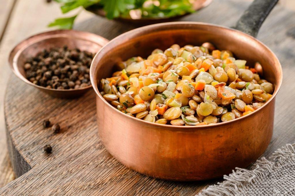 Пасту выложить в порционные тарелки, сверху выложить чечевицу, украсить помидорами и нарезанн.