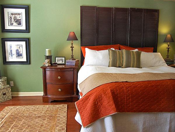 зеленый цвета стен в спальне с коричневого цвета полом и мебелью