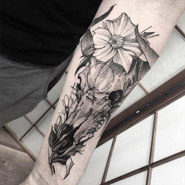 Татуировка на предплечье – череп животного с цветами в графике и дотворк
