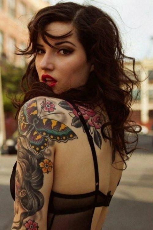 Шатенка с кудрявыми волосами со спины. На плече у нее большая татуировка в виде бабочки.