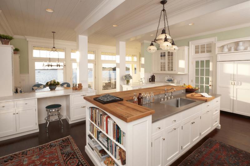 просторная белая кухня с коричневого цвета полом и большим двухуровневым островом с мойкой и столешницами из двух материалов