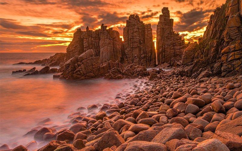 Каменные скалы в океане на закате солнца
