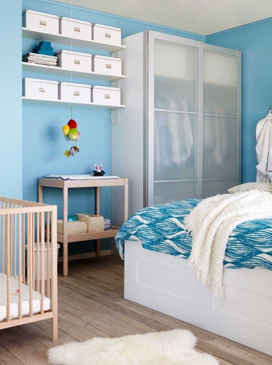Спальня с детской кроваткой в бело-голубых тонах.