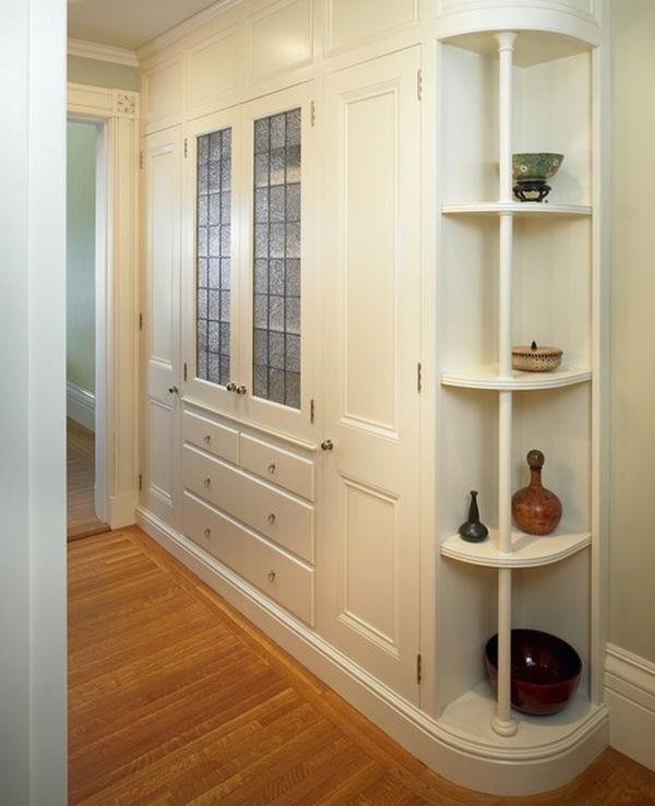 Белый шкаф с комодом и радиусными полками в небольшом коридо.