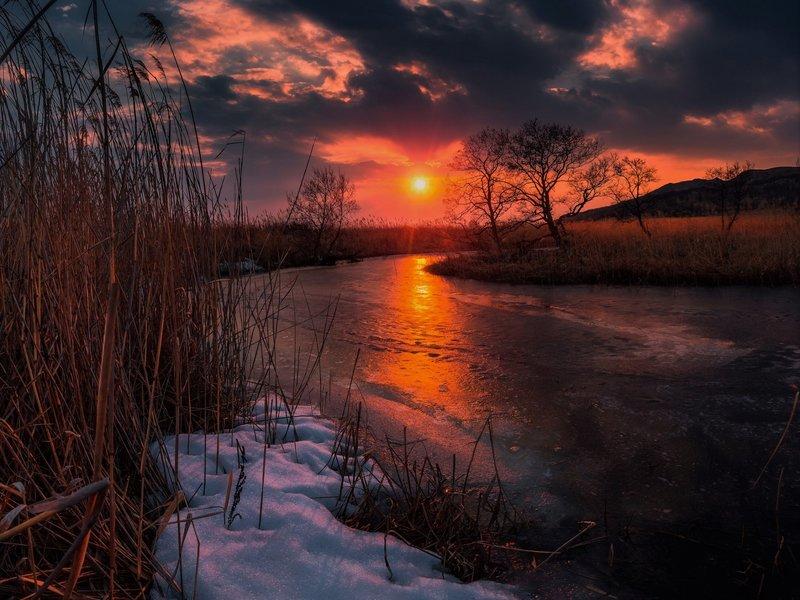 Закат солнца над покрытой льдом рекой
