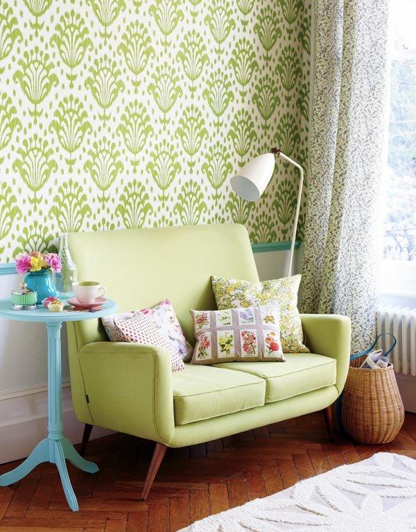 Зеленый диван на фоне стены с зеленым принтом в интерьере комнаты