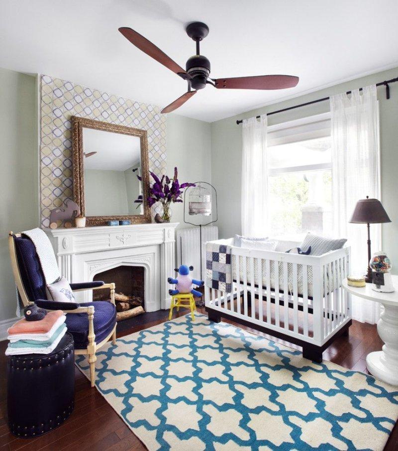 Спальня с детской кроваткой и камином.