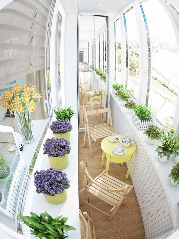 Балкон в белом цвете. столик и стулья на балконе. цветы на б.