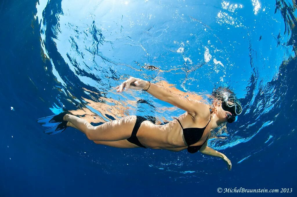 Woman swimming underwater in slow stock footage photo