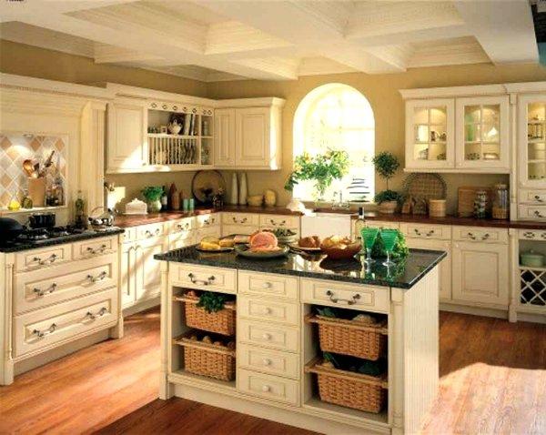 кухня кремового цвете в деревенском стиле с небольшим островом с черного цвета столешницей, нишами и ящиками