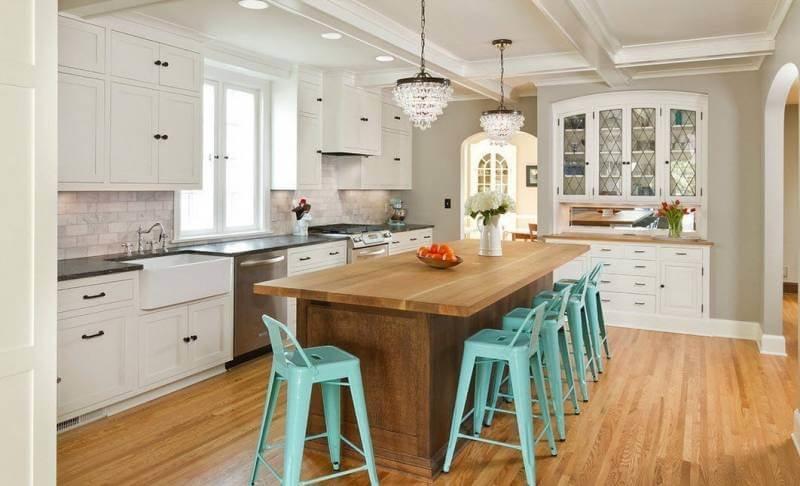 белая кухня с большим островом выполненным из дерева и стулями бирзового цвета