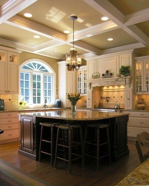 в светлом цвете кухня с высоким потолком, островом необычной формы с мраморной столешницей и барными стульями