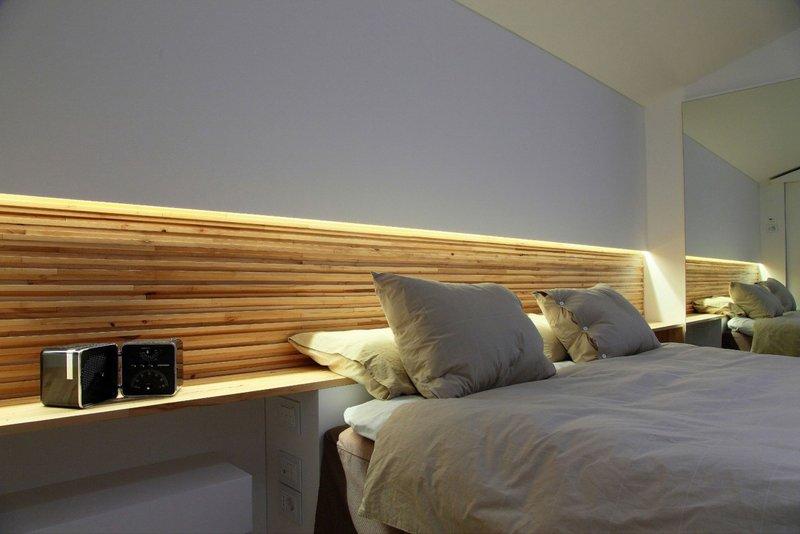 Подсвеченная ниша за кроватью в белой спальне