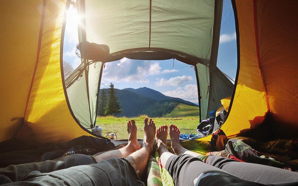 Красивая девушка лежит в палатке на природе