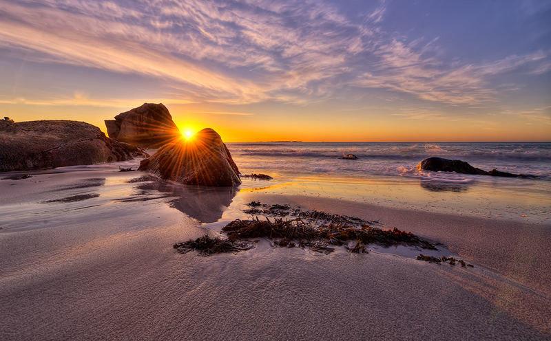 Камни на пляже на фоне восходящего солнца.
