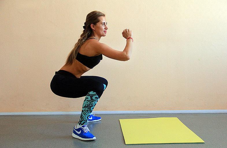 Во время приседаний колени должны быть согнуты под углом 90º и не выступать за носки, как будто вы садитесь на стул. Спину держите прямой. Ноги держите как можно шире, носки разверните наружу. В момент приседания максимально напрягите ягодичные мышцы.  4 повторения по 15 приседаний