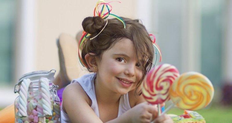 Улыбающаяся девочка с леденцами на палочке.