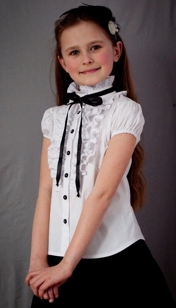 Белая блузка с черными пуговицами.
