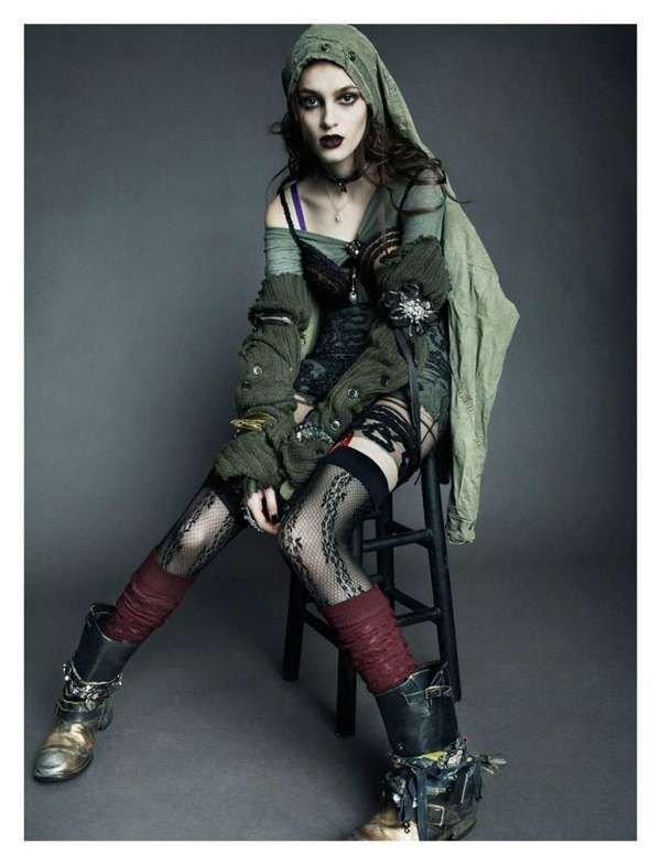 Модель в ботинках, черных чулках, зеленое мини платье, гетры на руках в стиле гранж