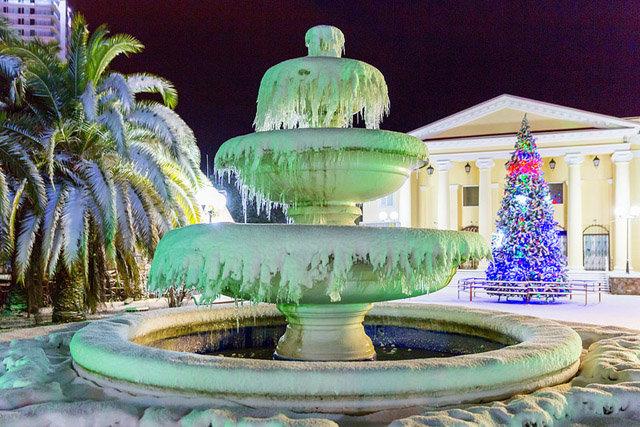Замерзший фонтан, а на фоне новогодняя ель в Сочи