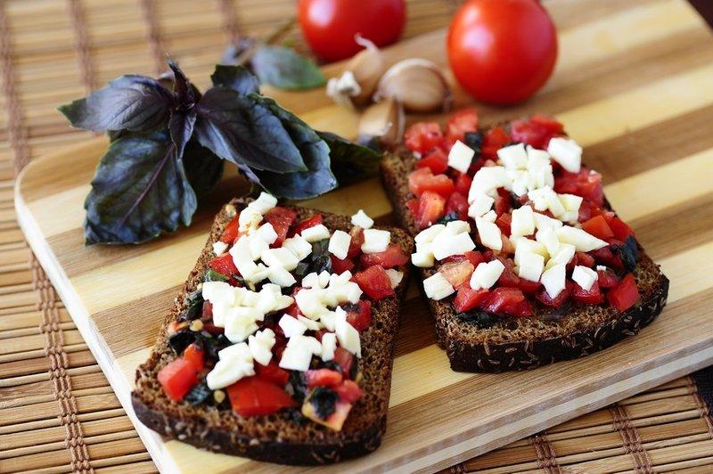 Брускетта — это популярная средиземноморская закуска, тост из запечённого хлеба с различными намазками и присыпками. Один из классических вариантов — брускетта с томатами и моцареллой
