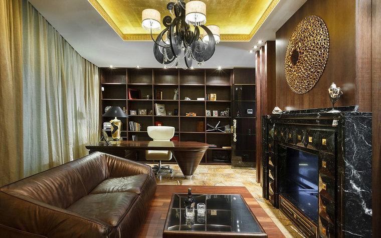 Кожаный диван и мраморный камин, дизайнерский стол и эффектные светильники. классики.