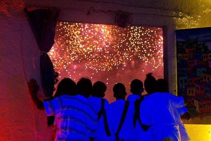 Молодые жители трущобы Паван-Паванзину смотрят праздничный фейерверк по случаю Нового года на пляже Копакабана в Рио-де-Жанейро, Бразилия.