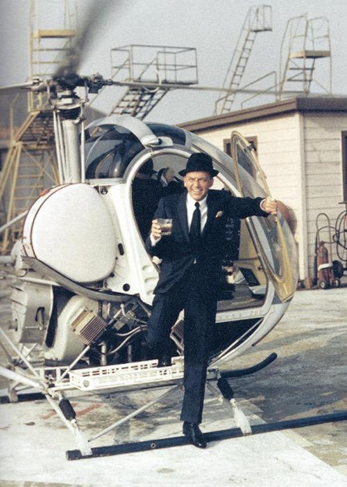Фрэнк Синатра выходит из вертолета с напитком в руке.