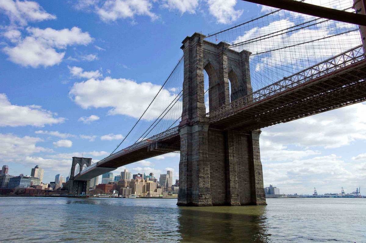 an overview of the suspension bridge between the east river from brooklyn to manhattan island