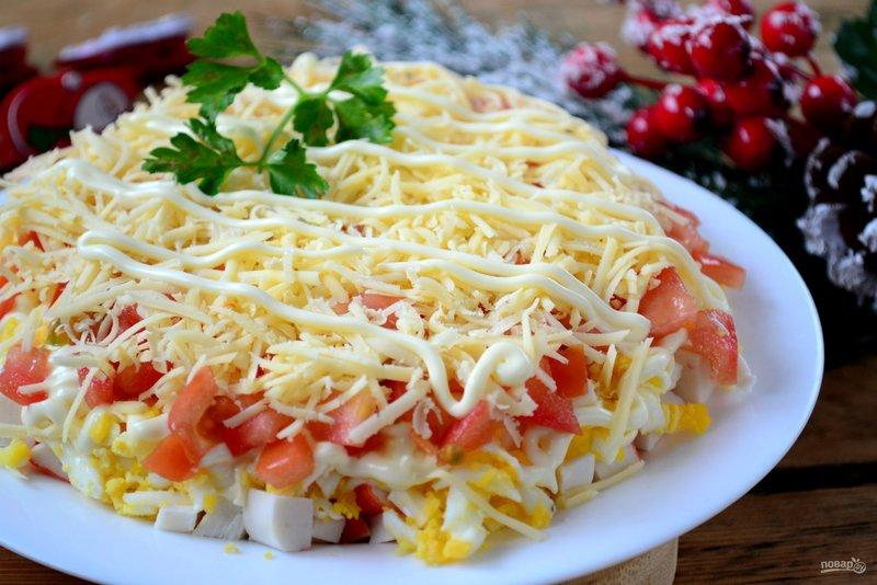 Праздничный салат с крабовыми палочками. Готовится он быстро и просто, а получается очень вкусным и сытным. Обязательно приготовьте его к новогоднему столу!