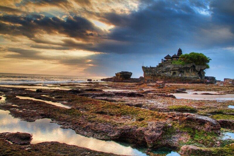 Храм Танах-Лот (Tanah Lot) - действующий индуистский храм, одна из основных достопримечательностей Бали, популярное туристическое место и культурный символ Индонезии. Танах Лот на балийском языке означает «Земля в море». Храм находится в 22 км от Куты и 20 км от Денпасара. Балийцы относят этот храм к одну из шести самых священных мест «sad kahyangan» на острове. Танах Лот на балийском языке означает «Земля в море».  Танах Лот входит в знаменитый ансамбль из нескольких храмов, расположенных на побережье Бали. Храмы построены таким образом, что из любого можно увидеть двух ближайших «соседей». Храмы, опоясавшие кольцом остров, оберегают его от злых морских духов, не давая им выходить из воды.  C сушей храм связан узким перешейком, пройти по которому можно только во время отлива. Только верующие люди могут подняться на лестницу, вырезанную в скале, и войти в храм. Туристы могут побывать только в нижней части скалы.  Существует 4 версии легенды происхождения храма:  1. Как и множество других храмов на Бали, Танах-Лот (Tanah Lot) связан с именем Нирартхи (одного из последних брахманов, прибывших на Бали с Явы в XVI веке). Именно Нирартхе, гласит легенда, храм обязан своим необычным местоположением: когда местный идейный вождь Бендеса Берабен стал забижать пришельца и велел тому убираться прочь. Нирартха послушался, но достаточно своеобразно: приказал скале, на которой он стоял (и где позже был возведен Танах-Лот), отчалить от берега… После этой убедительной демонстрации Бендесе не оставалось ничего, как признать верховенство Нирартхи…  2. Еще одна легенда гласит о том, что храм был построен тем же индуистским брахманом Нирартхи в 15 веке, который пришел к острову по пути, который ему указал божественный свет, исходящий из родника, бьющего из скалистого берега Танах-Лот. Этот ручеек сохранился до сих пор, его вода считается целебной. В скалистой основе острова обитают ядовитые морские змеи, которые, как полагают, охраняют храм от злых духов и незваных гостей.  3. По преда