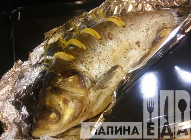 вкусная запеченная целая рыба толстолобик бескрайним