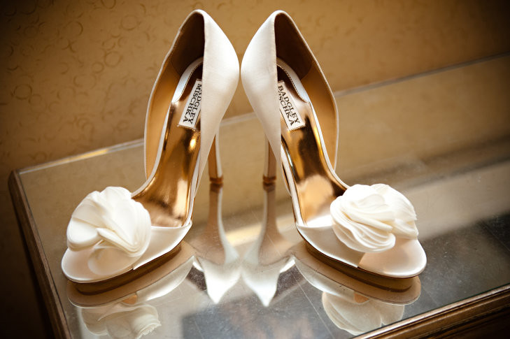 Свадебные бежевые туфли на высоком каблуке и с цветочной отделкой на передней части.