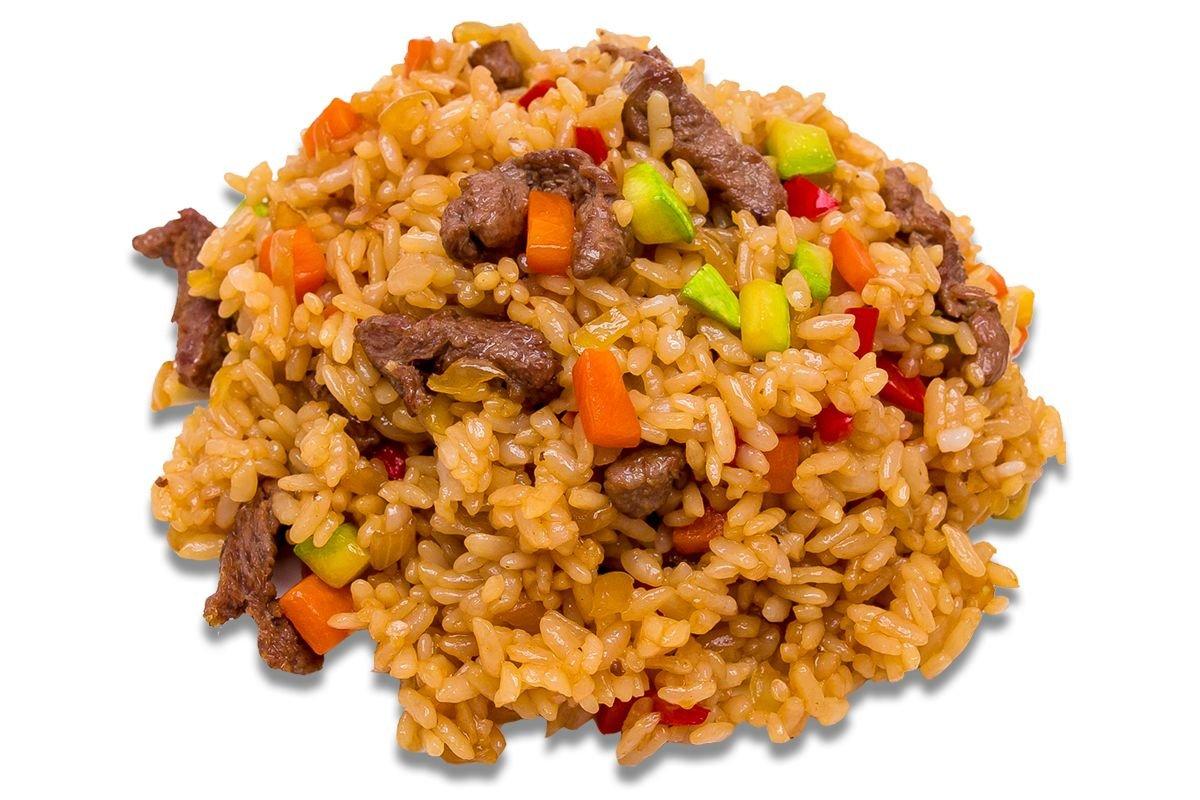 Промытый и замоченный рис добавьте к мясу в казан, равномерно распределив его поверх мяса.