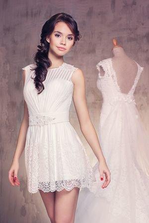 Короткое свадебное платье, которое как бы состоит из двух платьев: из платья футляр и надетого поверх него прозрачного, перехваченного красивейшим