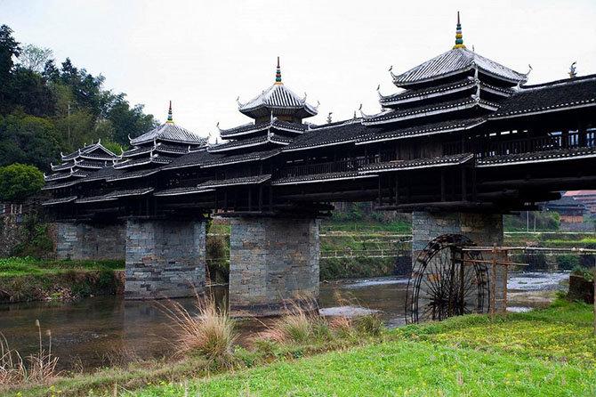 """Мост Шеньян Названный """"мостом Ветра и Дождя"""" и скрытый среди рисовых областей и гор, Шеньян находится в китайской провинции Гуангкси. Построенный в 1916 людьми Дуна, этническим меньшинством в Китае, мост украшен пятью отдельными структурами в виде пагоды. Традиционная китайская архитектура делает сооружение фантастическим, но самая удивительная вещь состоит в том, что во время строительства не использовался ни один гвоздь, а только архитектурные уловки"""