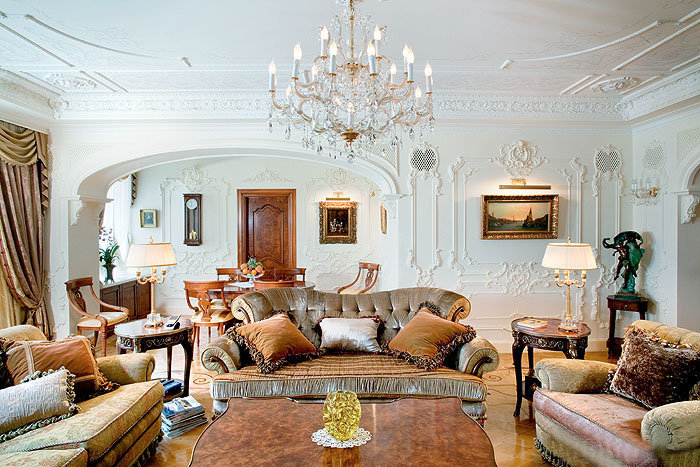 Белая просторная гостиная с серо-зеленой мебелью