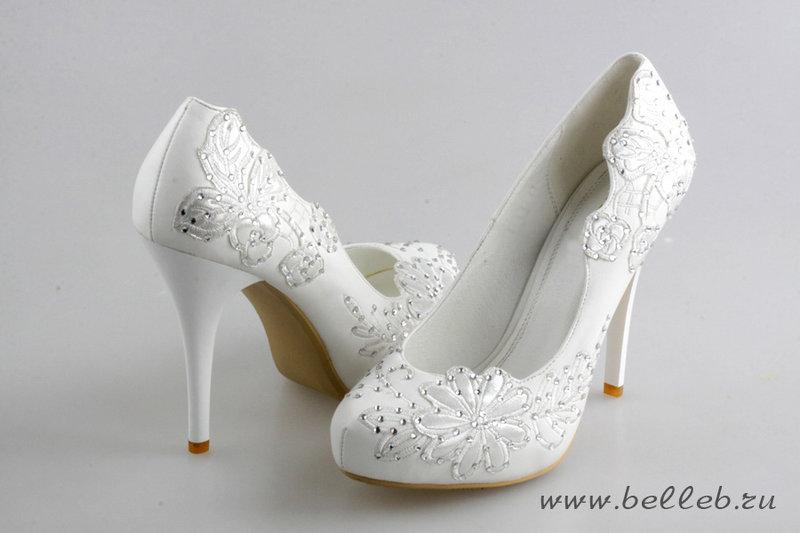 Роскошные свадебные туфли белого цвета на высоком каблуке и скрытой платформе.