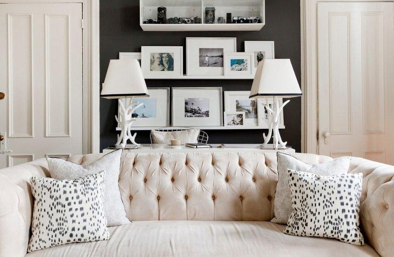 Белые полочки с фотографиями над нежно бежевым диваном.
