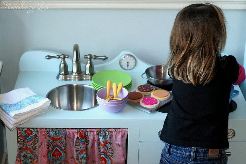 Девочка играет на своей детской кухне, которую можно сделать своими руками.
