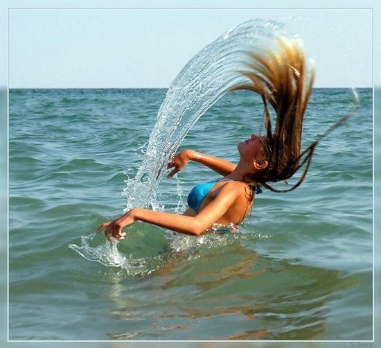 Девушка разбрызгивает воду волосами