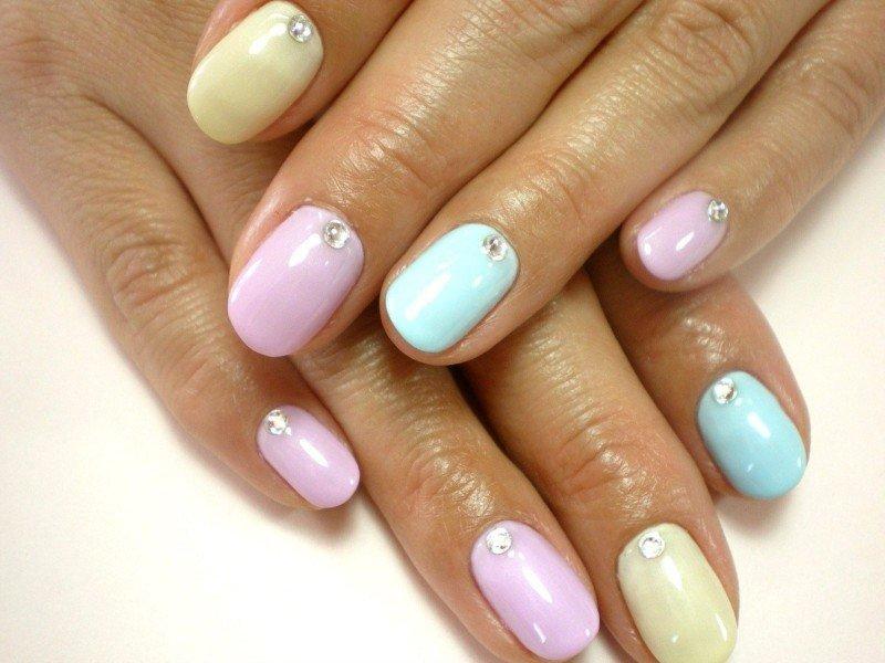 Радужный маникюр в постельных тонах. Мизинец и безымянный палец красим в бледно-сиреневый цвет, средний палец покрываем небесно-голубым цветом, ноготь указательного пальца красим бледно-желтым лаком, а большой палец – мятным.