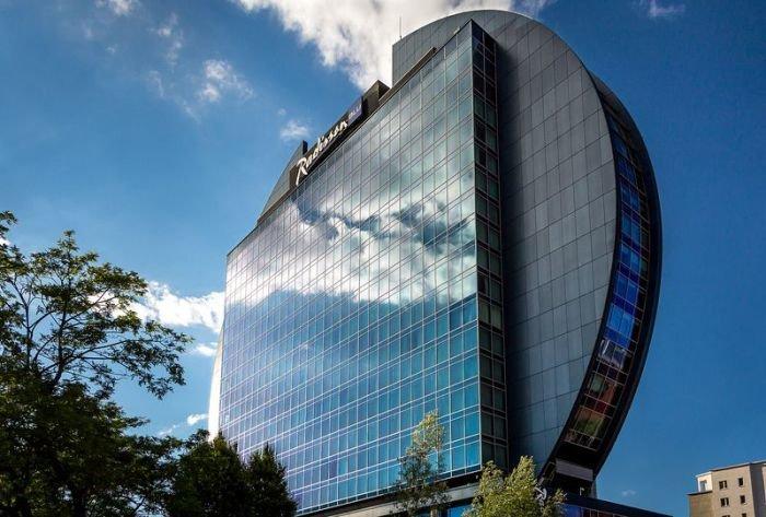Разработанная архитектором Джоном Сифертом дисковая структура отеля Рэдиссон в Германии выполнена из стекла, а по обе стороны фасада расположены дополнительные кубические структуры.