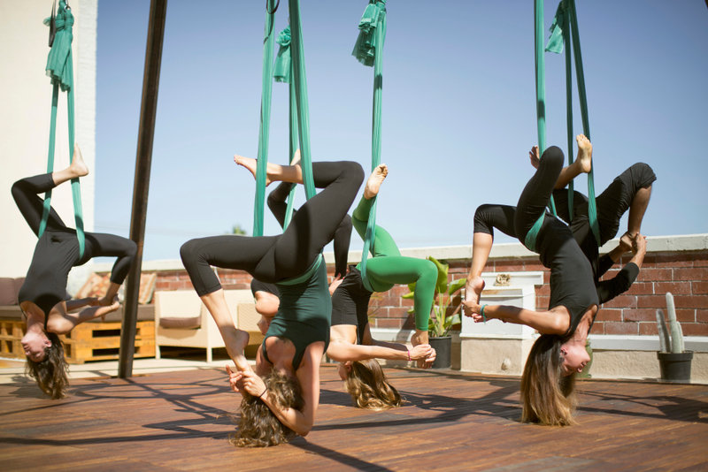 A group performs aerial yoga.