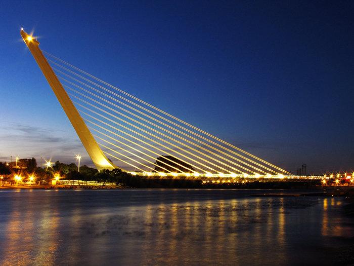 Знаменитый шедевр от испанца Сантьяго Калатравы, пешеходный мост Аламильо, был сооружен в 1992 году в Севилье. Уникальность 200-метрового полотна, проложенного через реку Гвадалаквир, состоит в том, что его вес держит всего одна опора и 13 натянутых стальных кабелей. В ночное время окрашенный полностью в белый цвет мост приобретает очень живописную окраску.
