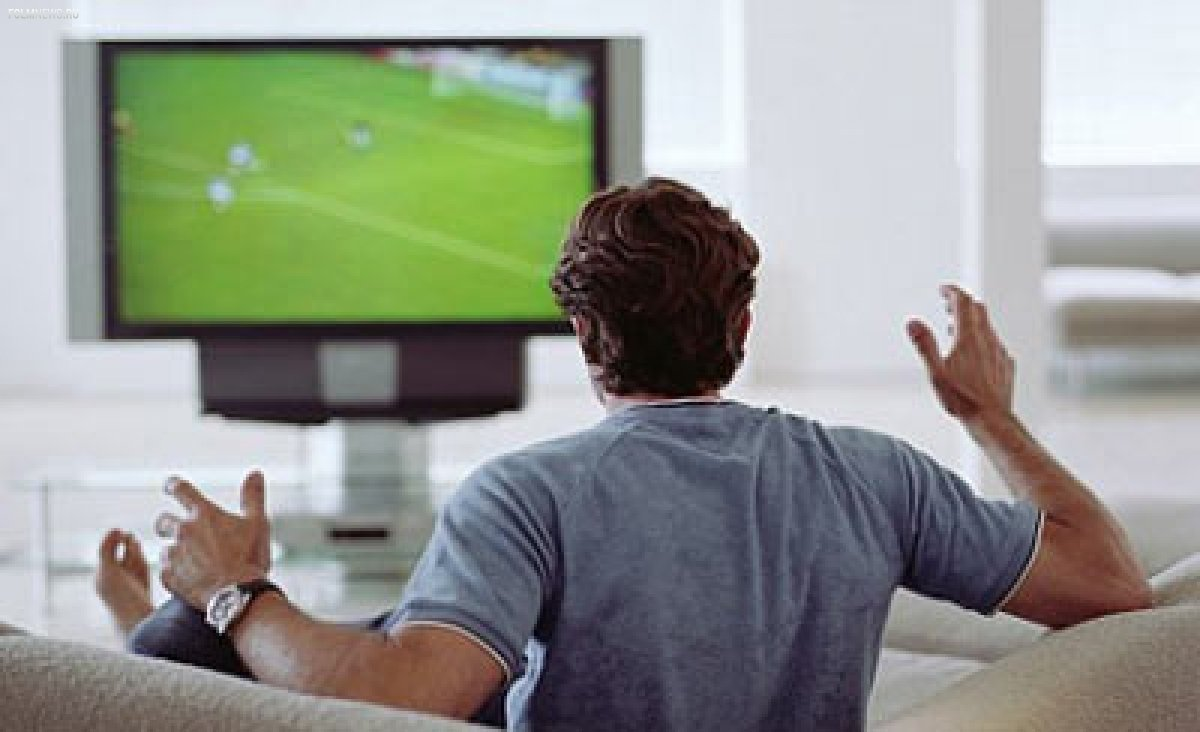 Болельщик смотрит футбол по телевизору