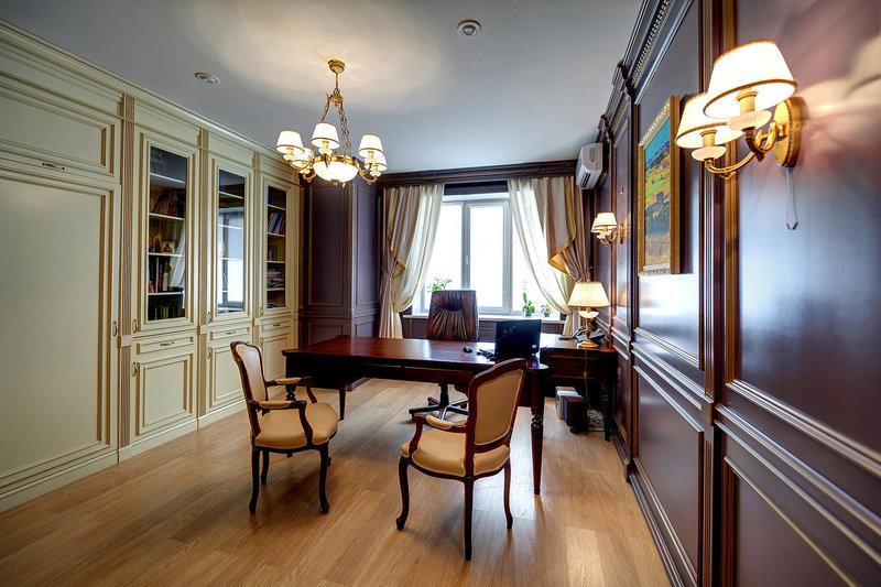 Кабинет не стандартный по цвету темный стол и светлые стулья.  Стены обшиты деревянными панелями под заказ фиолетового цвета.