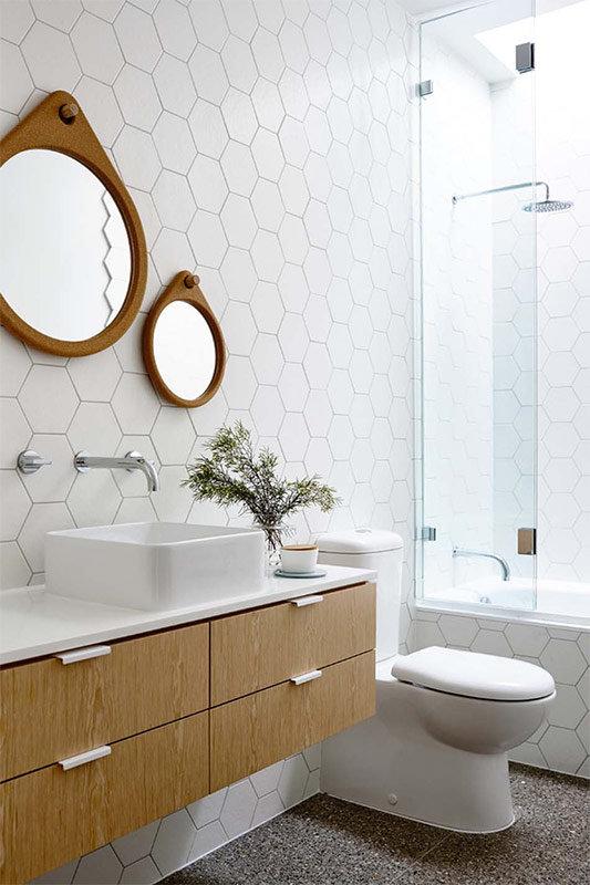 Белая шестиугольная плитка на стенах и мебель природного цвета светлого дерева, серый гранитный пол - сочетание цветов скандинавского стиля ванной комнаты.