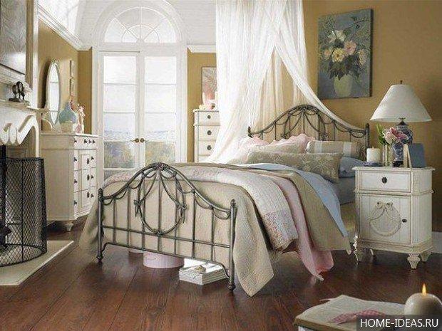 Кровать с кованными спинками и занавеской
