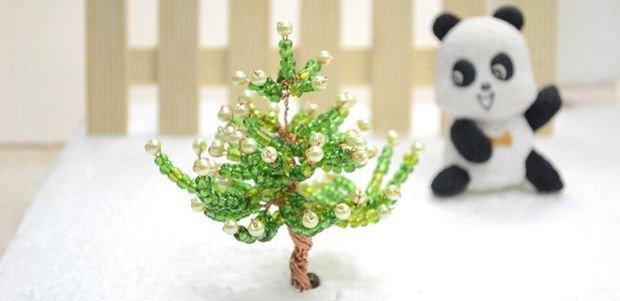 Миниатюрное новогоднее дерево, уже украшенное небольшими контрастными бусинами на концах лап, легко сделать из бисера.